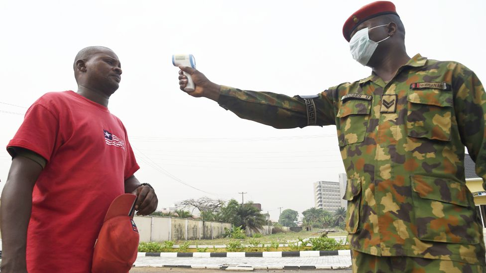 A soldier points a thermometer at a man at the Nigerian Army Reference Hospital in Lagos, Nigeria - Friday 28 February 2020