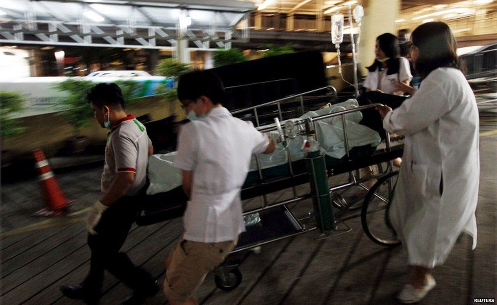 Medical workers rush the victim of a blast at the Erawan shrine to a nearby hospital in central Bangkok 17 August 2015