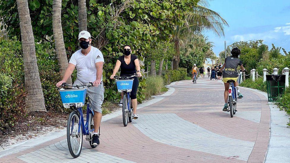Florida tourists in masks biking