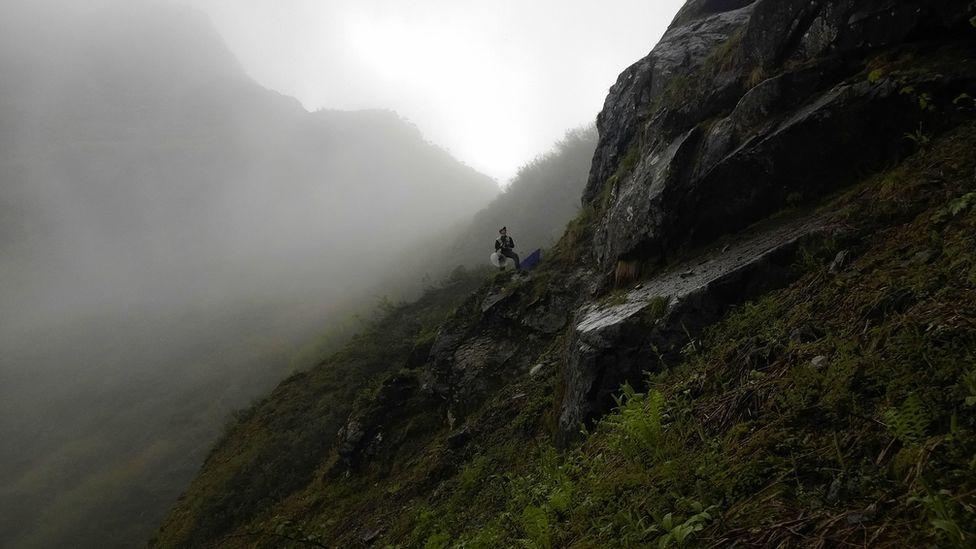 researcher on a steep hillside