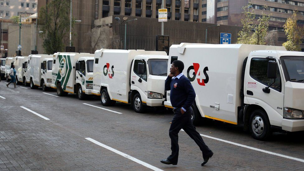 A cash-in-transit worker walks past armoured vehicles parked on the street during a nationwide protest following a spate of deadly heists this year, in Johannesburg, South Africa, June 12, 2018.