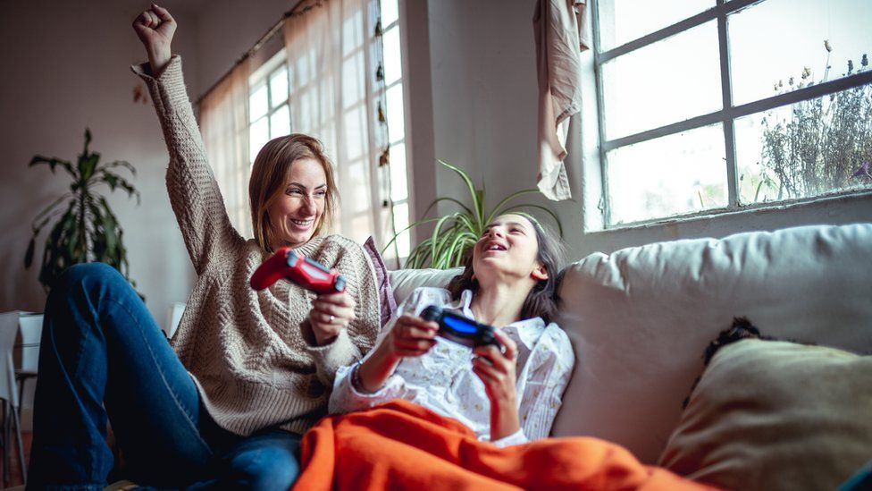 A mother and daughter play PlayStation
