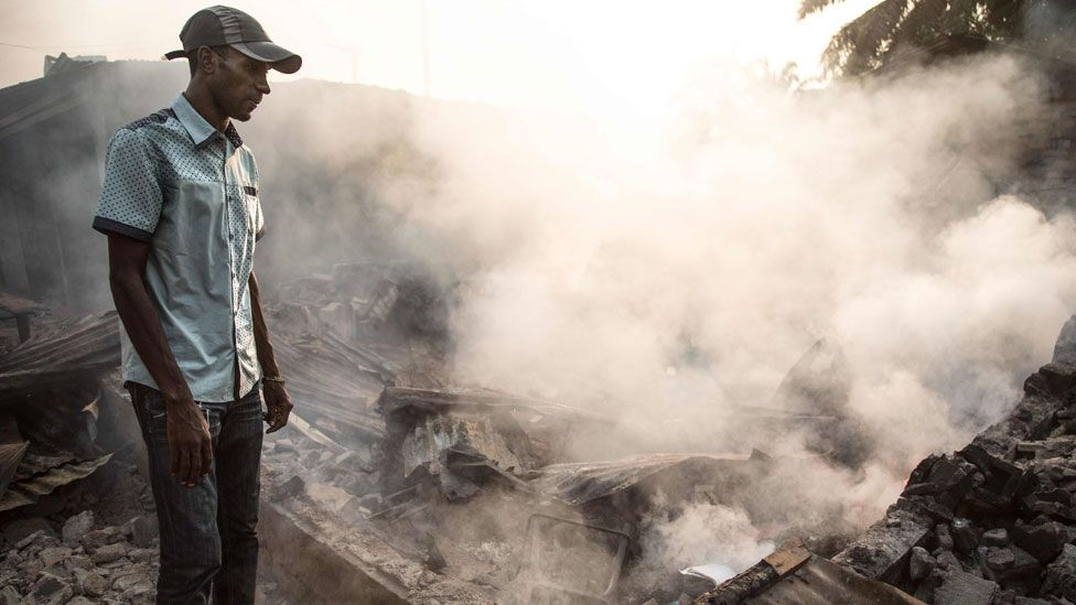 A man stand in front of a burnt down house in the PK5 district in Bangui on December 26, 2019, after clashes erupted when traders took up arms to oppose taxes levied by militia groups.