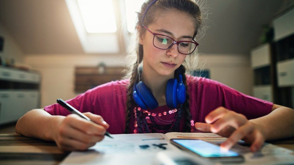 Girl doing school work with mobile