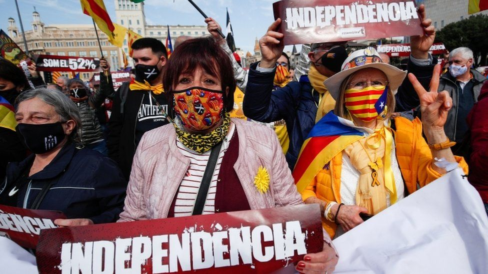 People hold signs during a protest to demand a pro-independence regional government in Catalonia, 28 February 2021