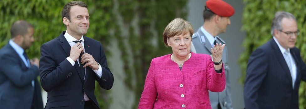 Emmanuel Macron and German Chancellor Angela Merkel walk to review a guard of honour upon Macron's arrival at the Chancellery (15 May)