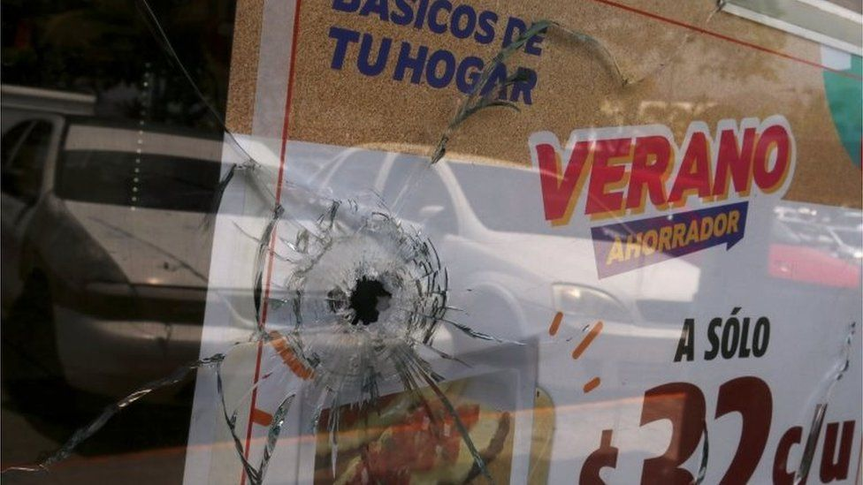 A bullet hole is seen in a window of a convenience store in Acapulco on 18 July, 2018.