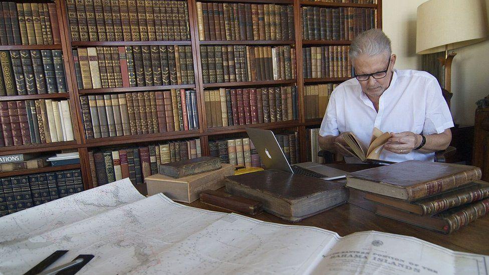 Josiah Marvel studying documents related to Columbus' voyage