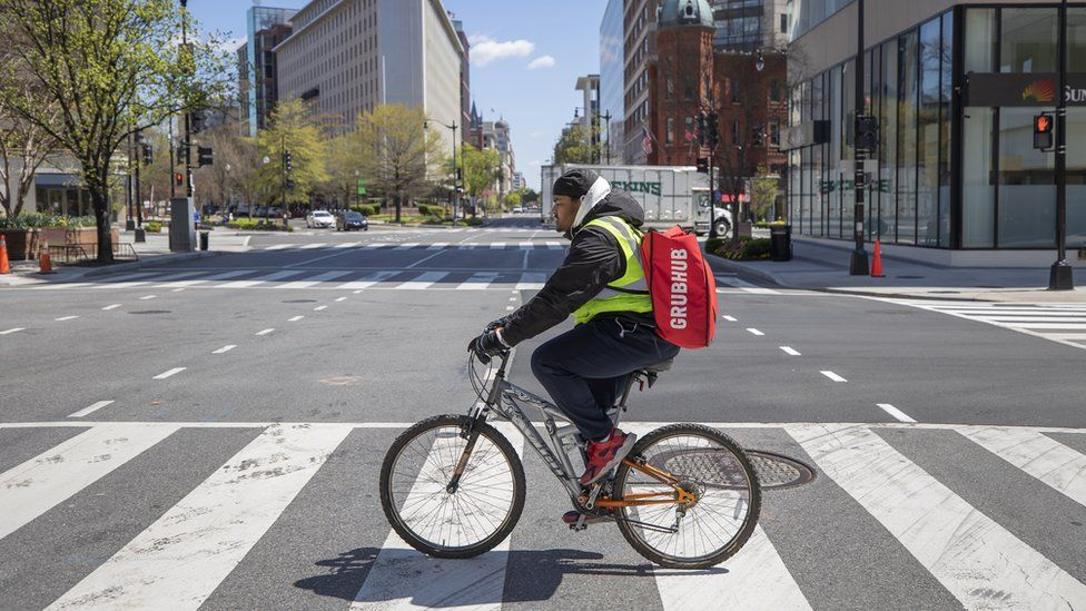 Grubhub delivery person Tayy Evans makes bicycle deliveries on the empty streets of Washington, DC, USA, 02 April 2020