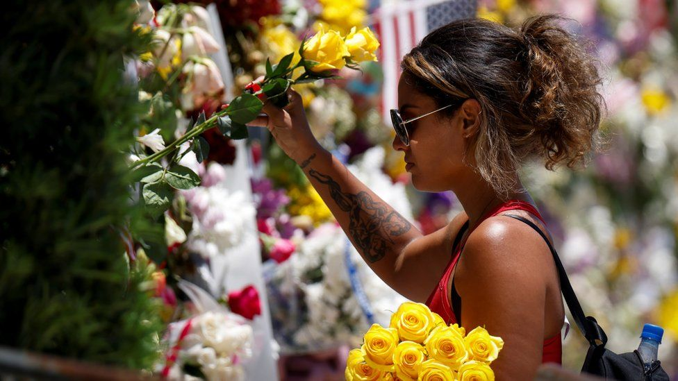 A woman mourns at a memorial site created by residents in front of a partially collapsed building in Surfside, Florida, 3 July 2021
