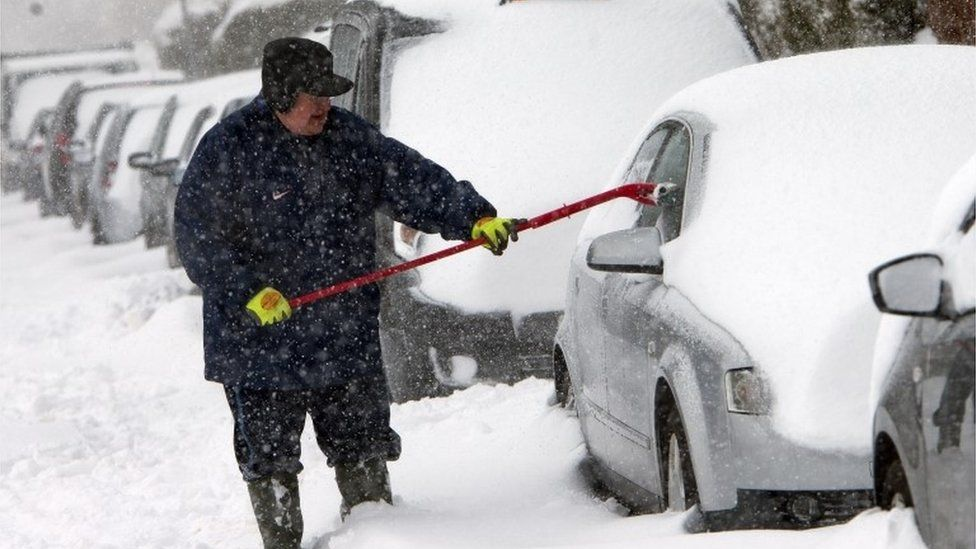 Man clearing snow from car in Glasgow