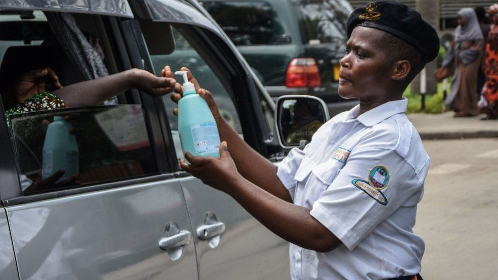 A security officer dispenses chlorinated water to a passenger at Muhimbili National Hospital in Dar es Salaam