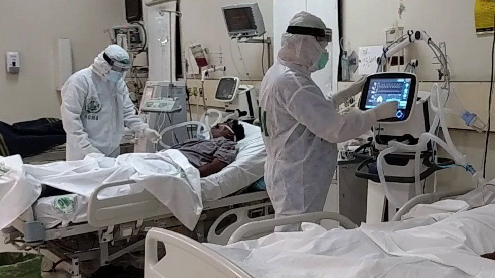 Two doctors work on patients in intensive care