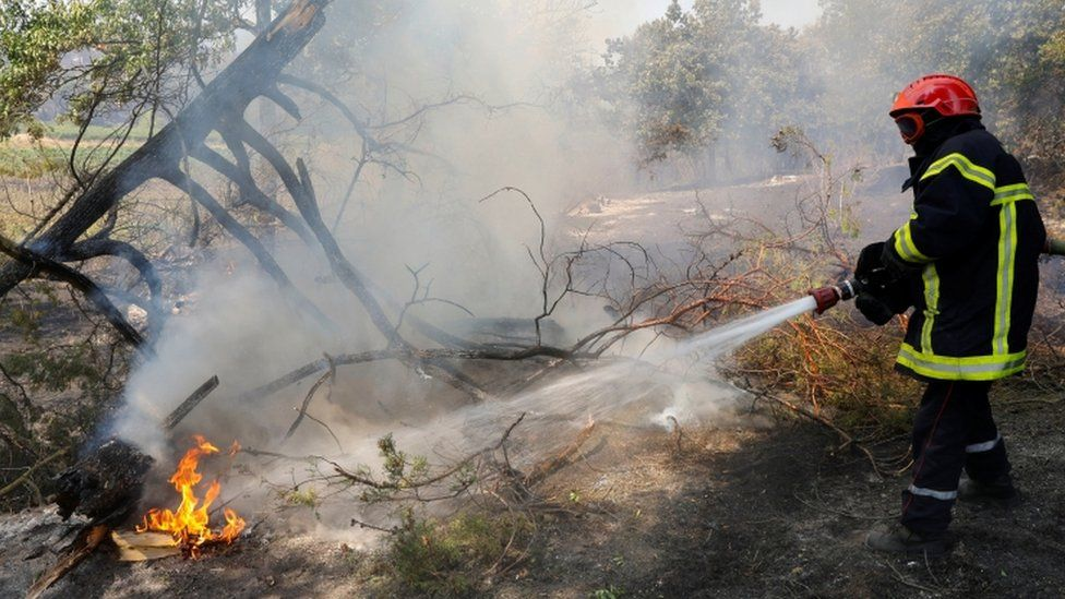 A firefighter extinguishes a fire that broke out in Cogolin in the Var region of southern France