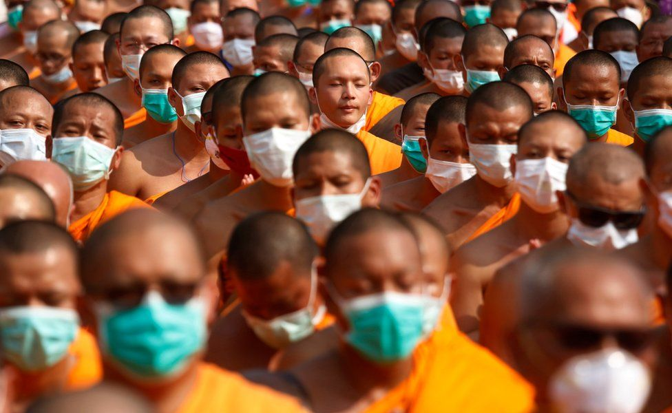 Buddhist monks of the Dhammakaya sect temple pray as they confront with Thai policemen outside the temple in Pathum Thani, north of Bangkok, Thailand, Monday, 20 February 2017.