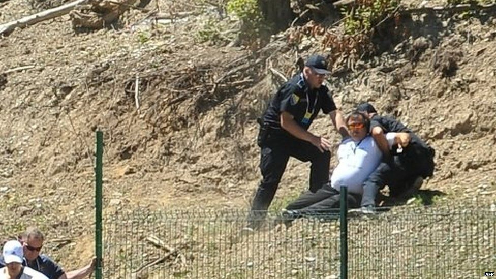 Bosnian police officers arrest a protester suspected of having taken part in the attack on Mr Vucic