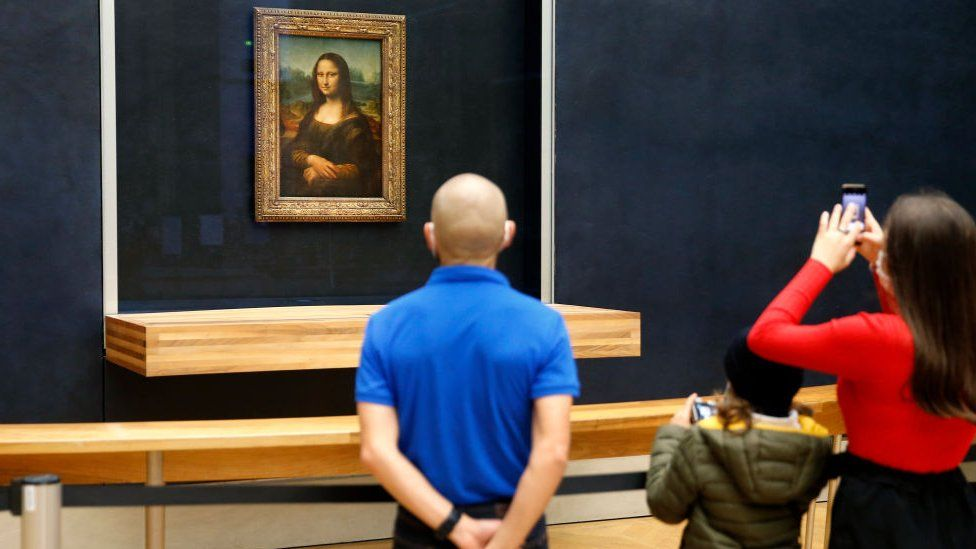 Tourists look at the Mona Lisa