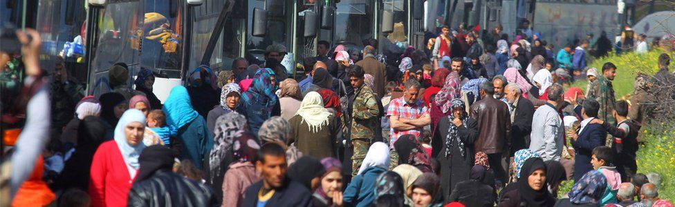 People that were evacuated from the two villages of Kefraya and al-Foua walk near buses, after a stall in an agreement between rebels and Syria's army