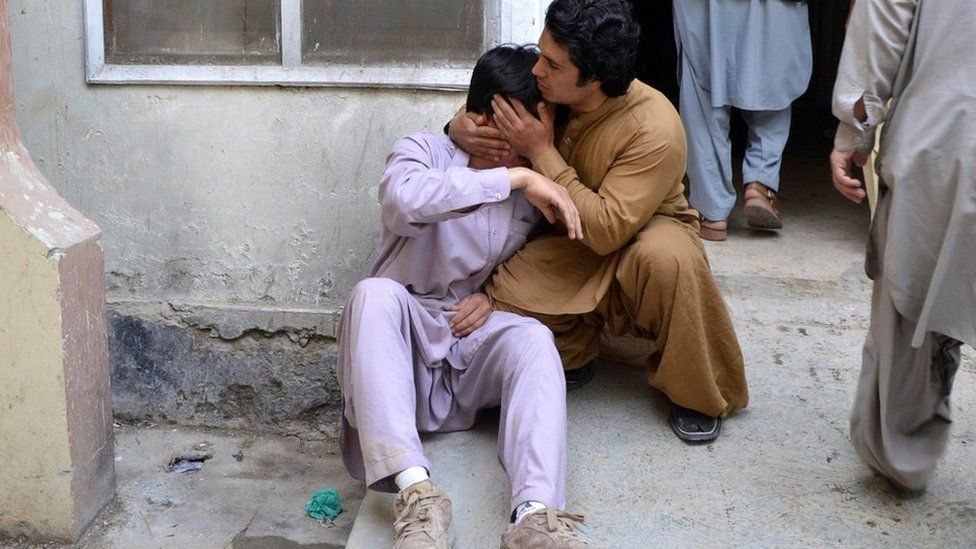 Men mourn in Quetta after the attack, 12 April