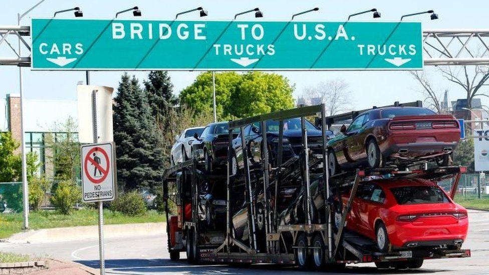 Car transporter heading for Detroit, Michigan, drives on the lane to Ambassador Bridge in Windsor, Ontario, Canada