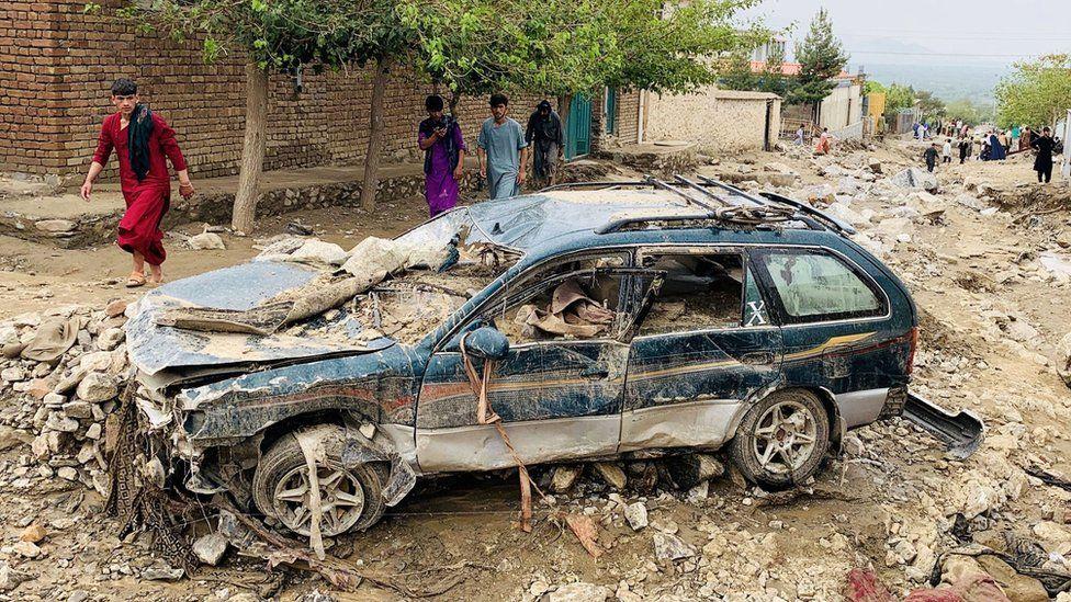 An Afghan man walks past a damaged car after floods in Charikar