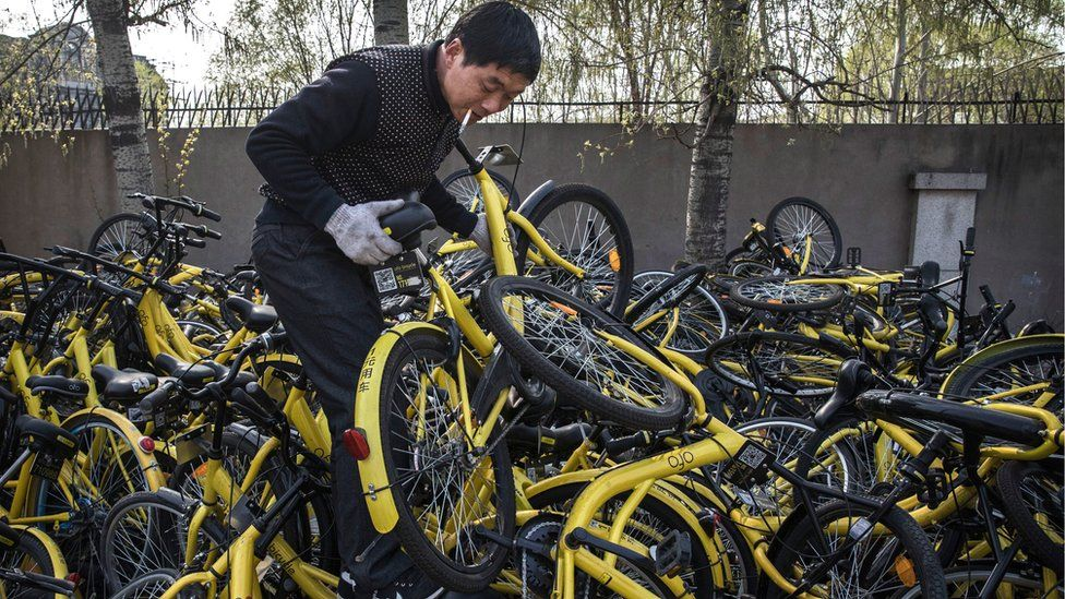 A man holds a broken bike from the Chinese bike sharing scheme