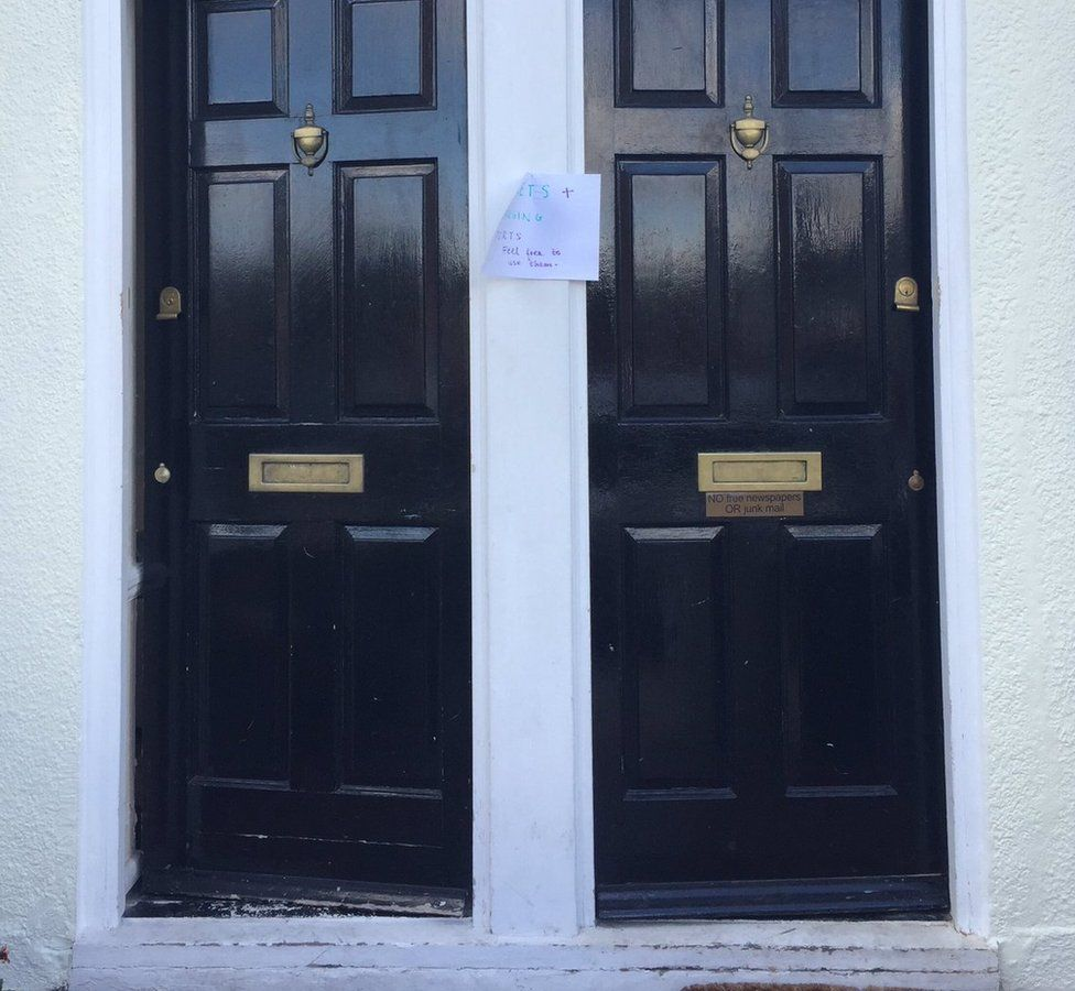 Double doors with a sign offering toilets, tea and charging ports