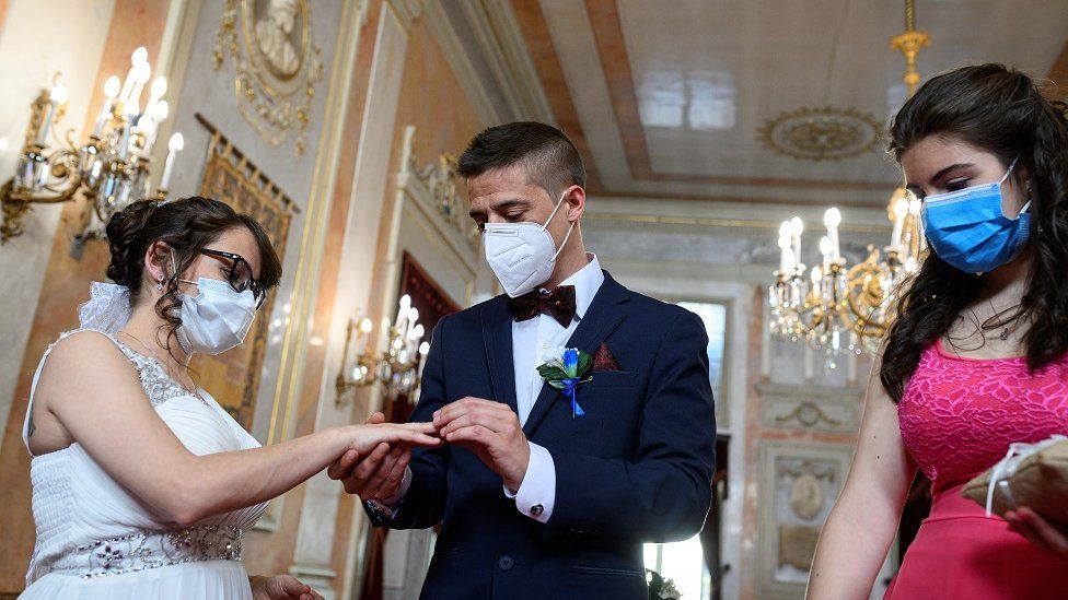 Groom Iker (R) places a wedding ring on the hand of bride Aranzazu (L) as the bridesmaid (R) looks on during their civil wedding at the town hall of Alcala de Henares, Madrid, Spain, 06 June 2020. The nuptial ceremony was one of the first held there since the the state of emergency was implemented in March throughout Spain due to the pandemic COVID-19 disease caused by the SARS-CoV-2 coronavirus.