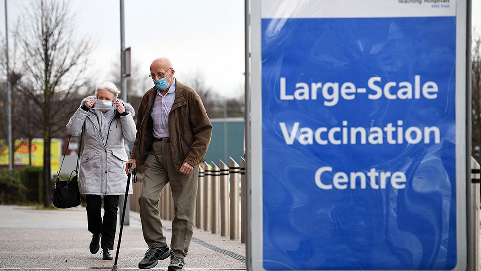 People arrive at a mass vaccination centre in St Helens in northern England on 18 January