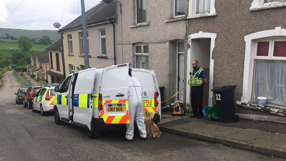 A row of terraced houses - an officers stands guard in front of a house where there is a wheeley bin with the number 22 on it. A forensic officer in forensic clothing is looking in the back of a police van