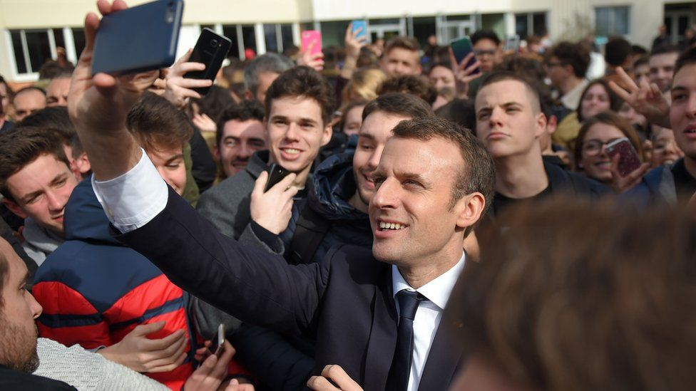 French President Emmanuel Macron takes a selfie with students at the high school Therese Planiole, in Loches, central France, on March 15, 2018