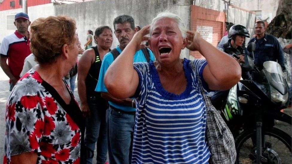A relative of a prisoner cries in front of a police station in Valencia on March 28, 2017, after a fire engulfed police holding cells that resulted in the deaths of 68 people