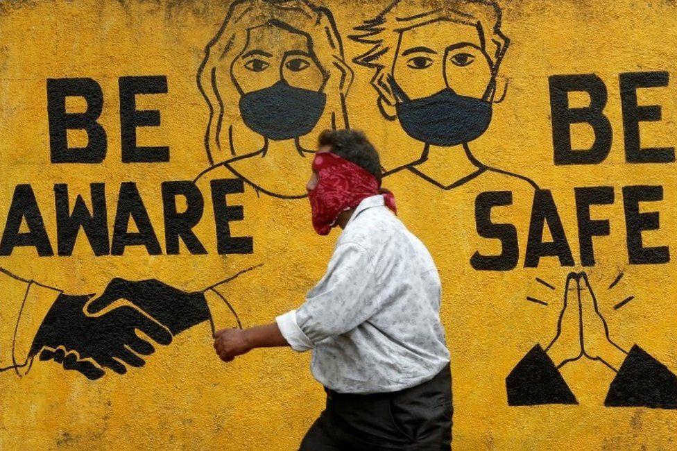 A man walks past a graffiti amid the spread of the coronavirus disease (COVID-19) in Mumbai, India, November 2, 2020.