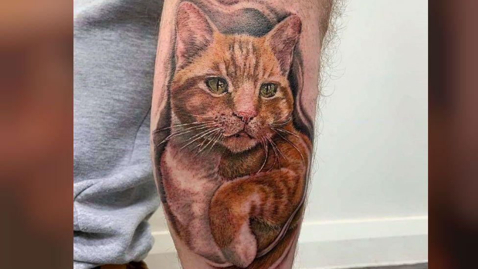 Tattoo of cat on man's leg