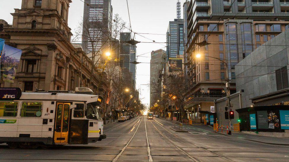 A tram crosses a deserted street in central Melbourne during lockdown