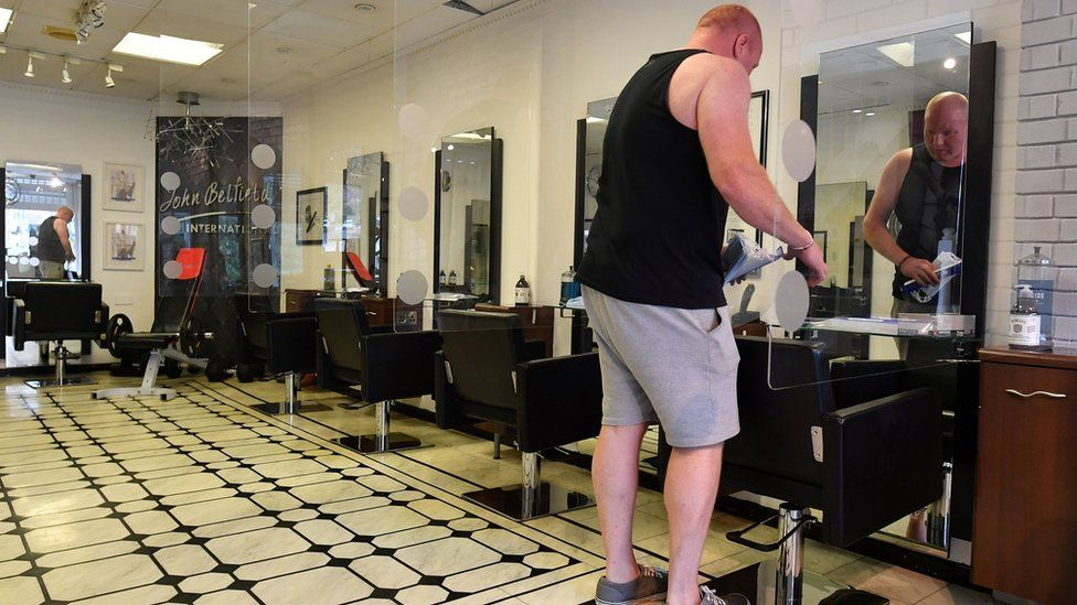 Hairdresser John Belfield prepares his hair salon, adapted with perspex screens in between customers' seats, in Newcastle-under-Lyme