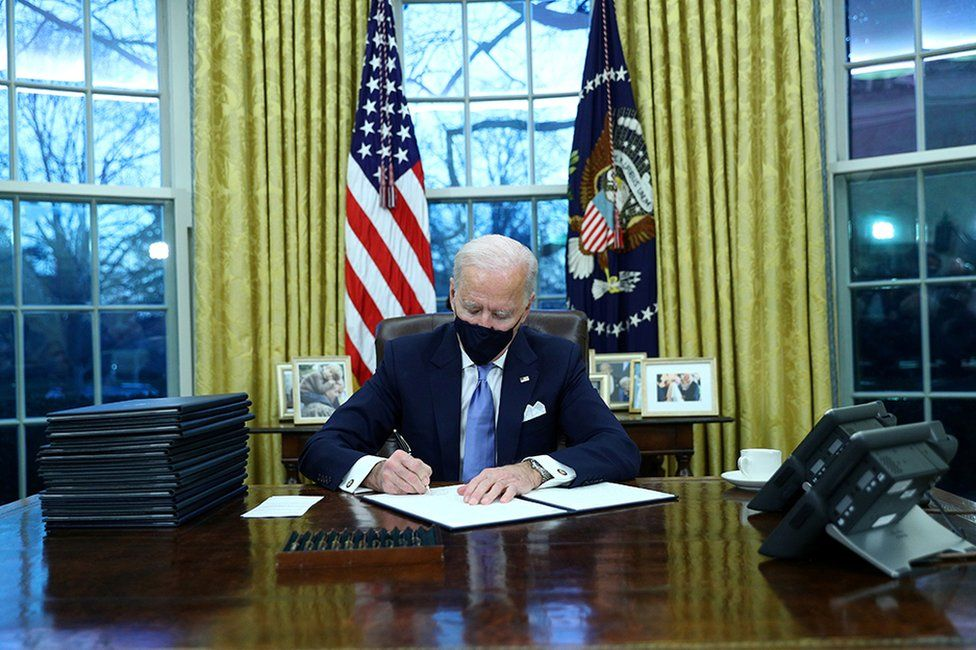 US President Joe Biden signs executive orders in the Oval Office of the White House in Washington, after his inauguration as the 46th President of the United States, 20 January 2021.