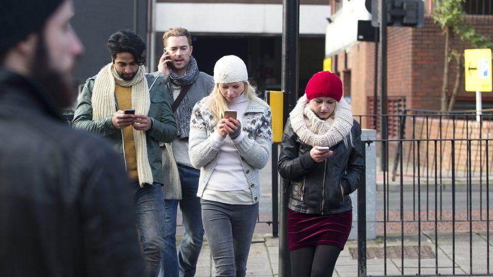 People crossing the road looking at mobile phones