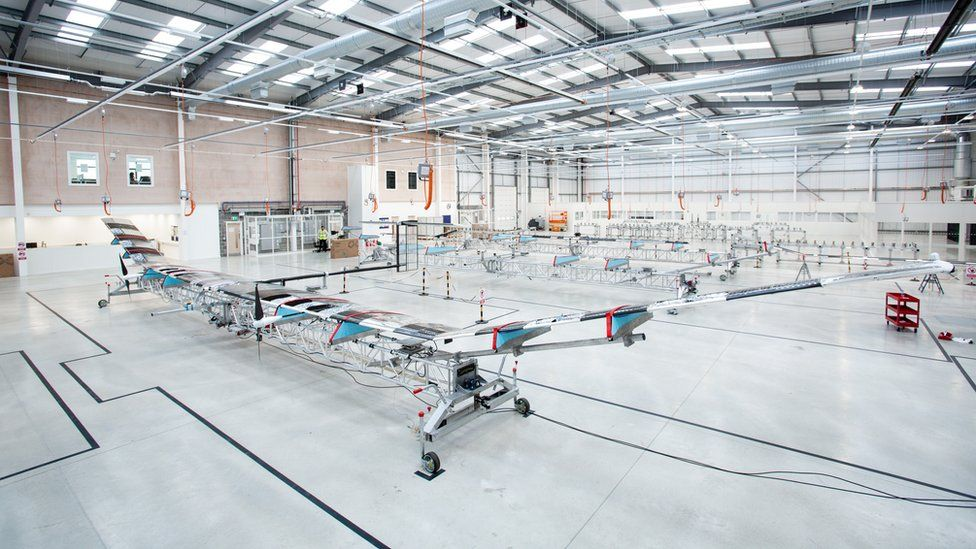 A manufacturing floor with a long, transparent glider-like plane visible in the foreground