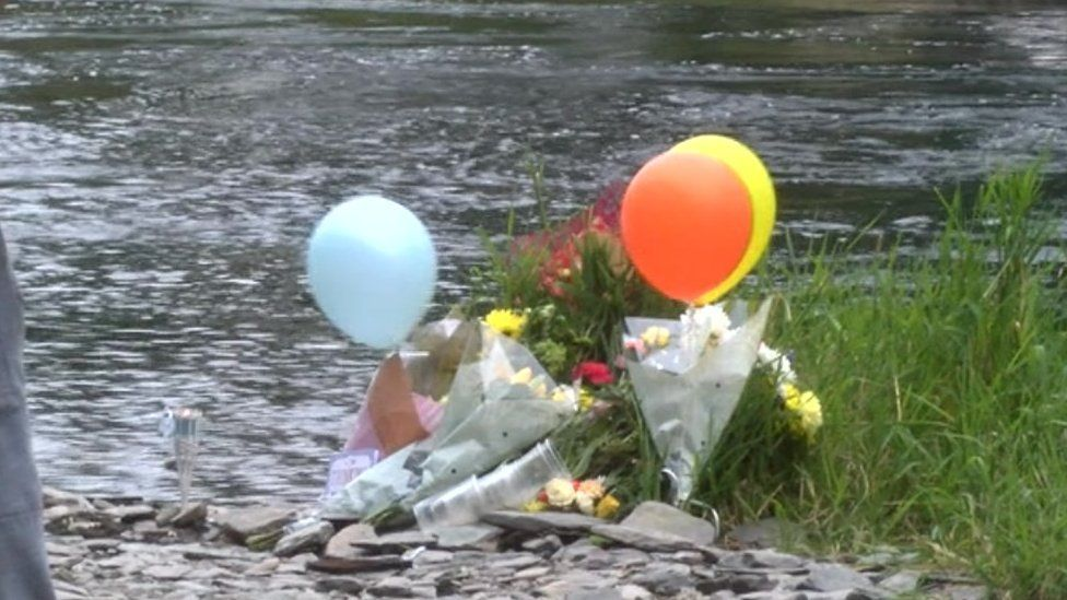 Balloons and flowers were left at the river bank in Newcastle Emlyn