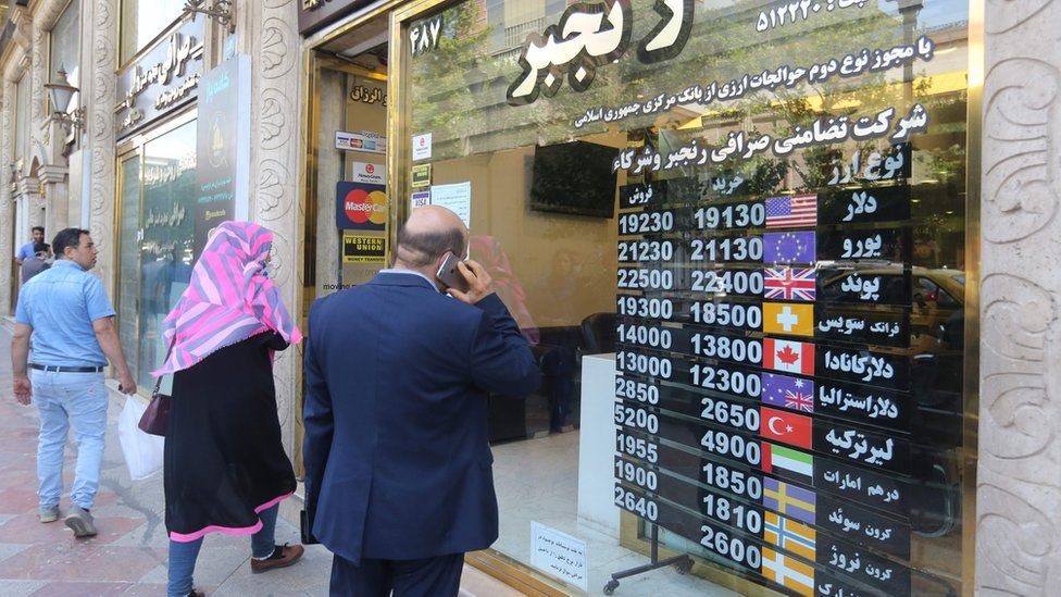 Iranians wait outside a money exchange office in Tehran amid the ongoing COVID-19 pandemic, on June 22, 2020