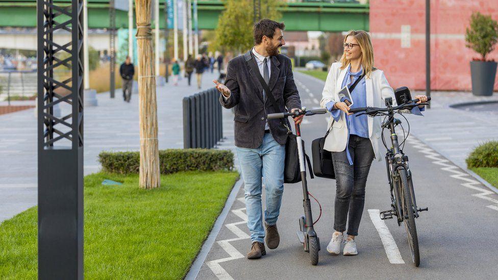 couple talking, on e-bike and e-scooter