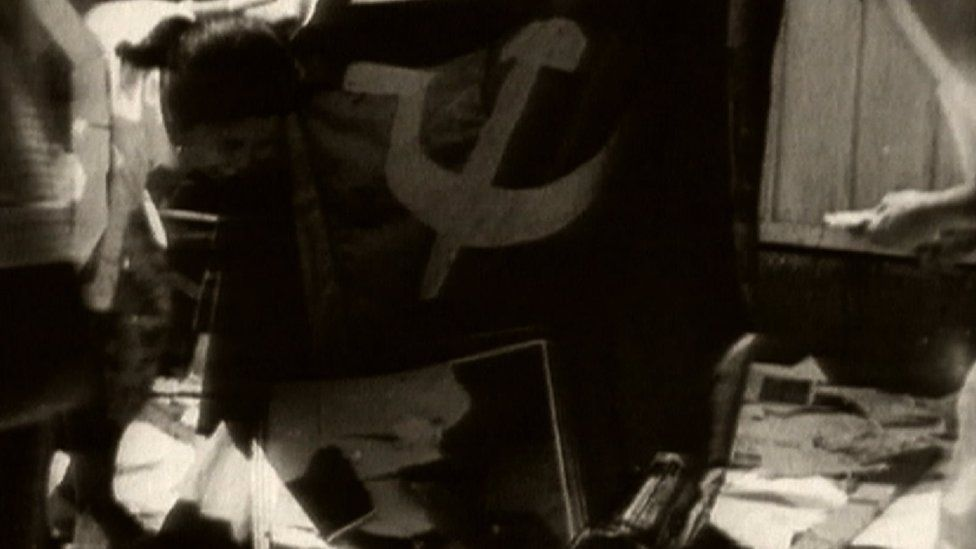 Black and white picture of a communist flag, taken from footage at the time.