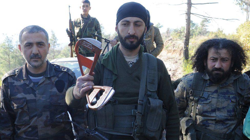 Rebels show parts of a parachute near the northern Syrian village of Yamadi, 24 November