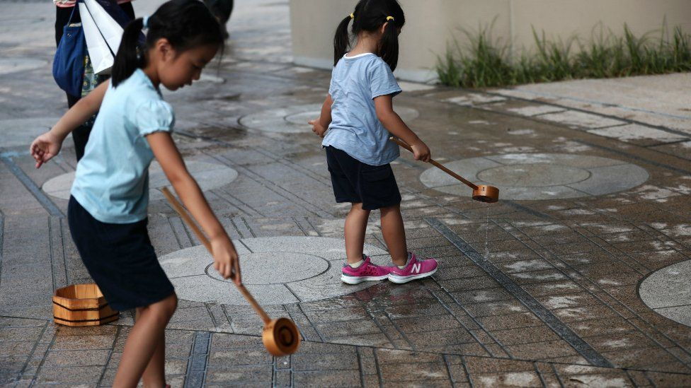 Japanese girls splash water on the ground during a water sprinkling event called Uchimizu which is meant to cool down the area, in Tokyo on July 23, 2018.