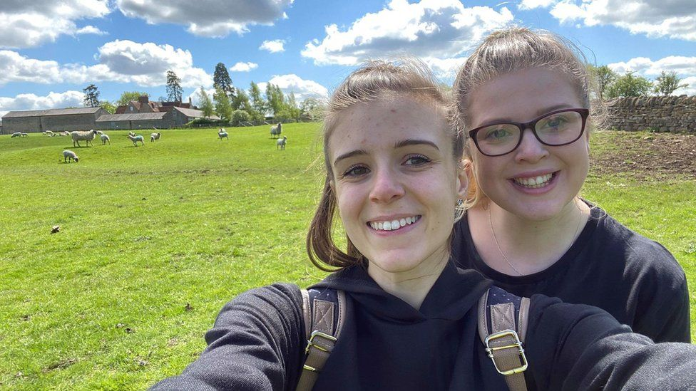 Danielle Kinton and her partner with sheep in the background