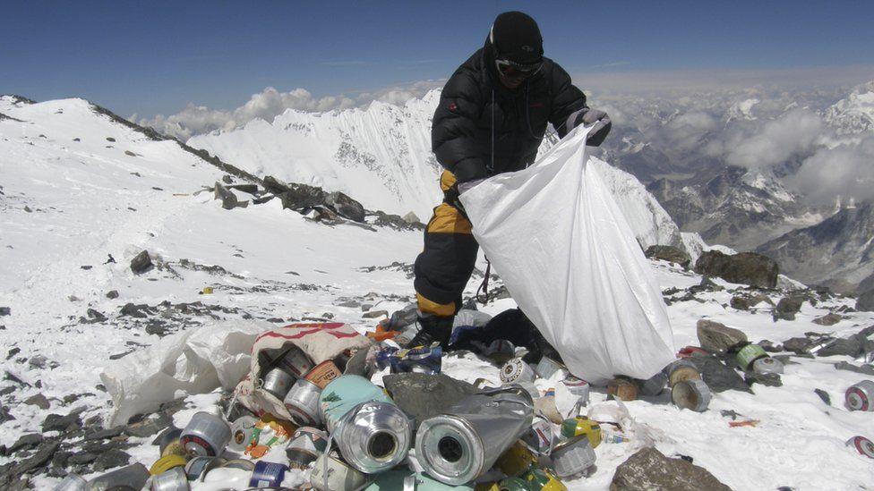 Nepalese sherpa picking up trash on Everest