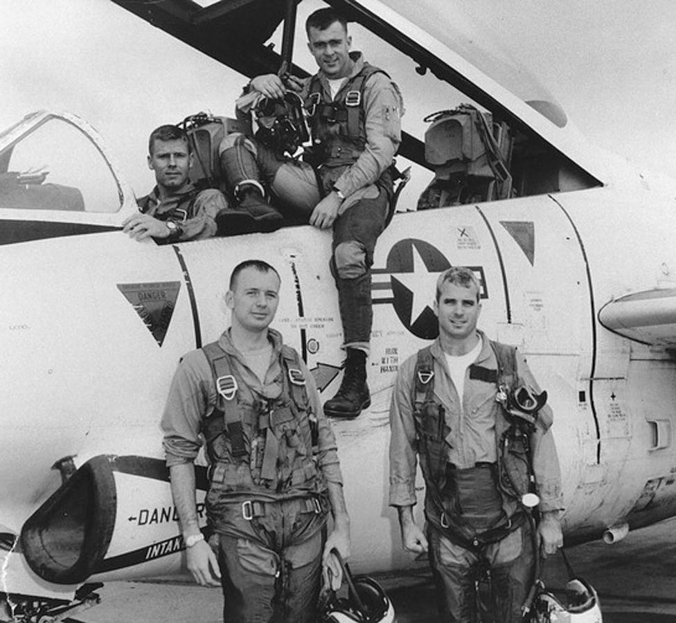 """John McCain with Squadron members and a North American T-2 """"Buckeye""""."""