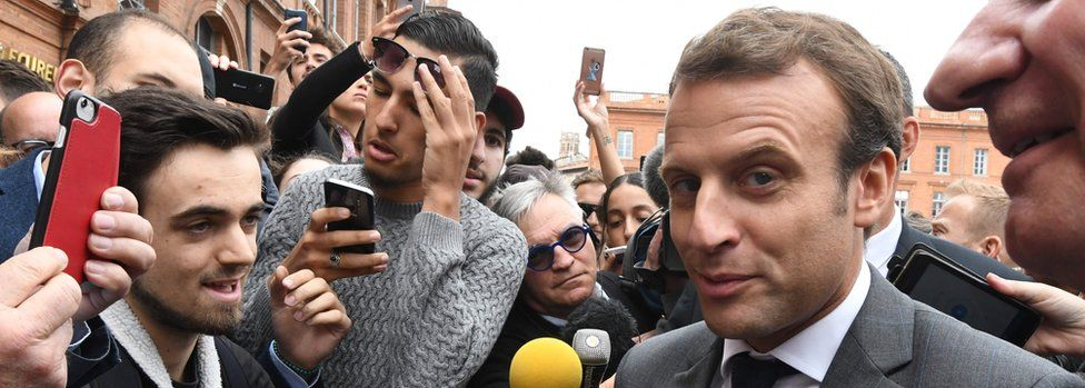 French President Emmanuel Macron speaks with people at the Place du Capitole in Toulouse, southern France