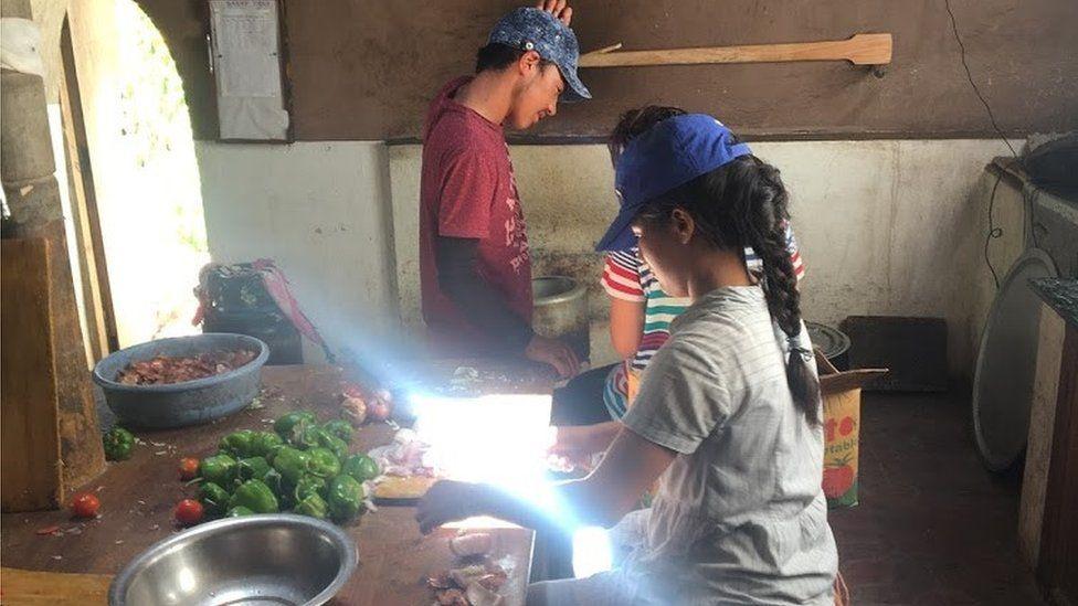 Child helping prepare food in kitchen